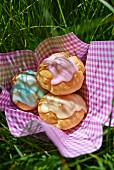 Choux pastries with colourful glacé icing on a napkin in the grass