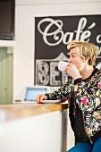 Frau sitzt an der Bar eines Cafes und trinkt Kaffee