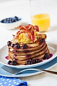 Blueberry Pancakes Topped with Egg and Bacon; Orange Juice