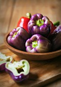 Purple and Red Bell Peppers in a Wooden Bowl