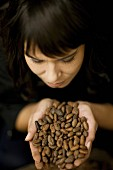 A woman holding cocoa beans in her hands