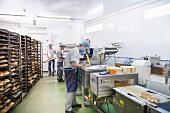 Arbeiter in Bäckerei mit Brotregalen & Verpackungsmaschine