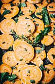 Sweet potato slices with herbs on a baking tray