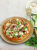 A pan-cooked pizza with satay chicken