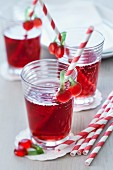 Cherry juice spritzer in glasses with straws decorated with cherry jelly sweets