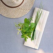 Fresh garden herbs with a napkin and a straw hat