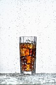 A glass of cola with ice cubes in a rain shower