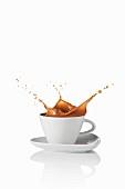 Milchkaffee spritzt aus der Tasse