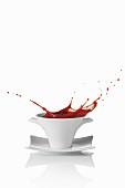 Tomato soup splashing out of a soup bowl