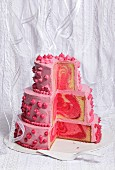 A three-tier pink wedding cake, sliced open