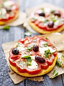 Mini pizzas with beef tomatoes, olives and pesto