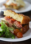 An Italian sandwich made of sweet potato bread with Parma ham and basil pesto