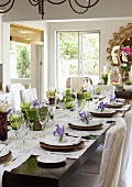 A festively laid table with green wine glasses and decorated with purple irises, white lilies and pots of herbs