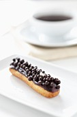 An éclair topped with chocolate balls
