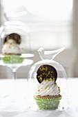 Cupcake mit Sahne und Schokotaler unter Glashaube
