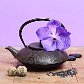 Cast-iron teapot with a purple orchid