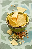 Tortilla chips in a bowl with corn kernels to one side