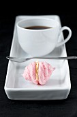 cup of coffee with small pink meringue