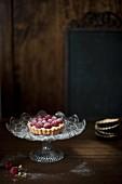 Small raspberry tart on a glass cake stand