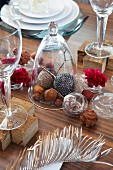 Nuts and decorative baubles under a glass cloche and pralines, flowers and a feather on a table decorated for Christmas