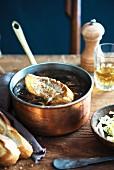 Französische Zwiebelsuppe mit Baguettescheibe in Kupfertopf