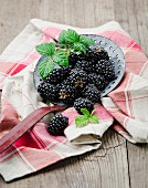 Fresh blackberries on a draining spoon and on a tea towel