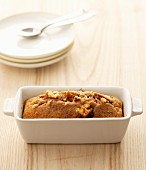 Banana cake with pecan nuts in a porcelain baking dish