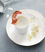Chilled cream of cauliflower with a strip of bacon