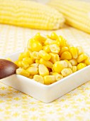 Sweetcorn in a small dish in front of corn cobs