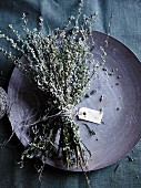 Dried mugwort, tied in a bunch with a label, on a plate