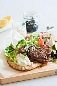 Lamb chop on pita bread, with a Greek salad and tzatziki