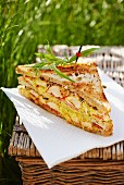 A club sandwich with lobster on a picnic basket