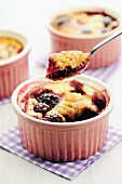 Blackberry clafoutis in ramekins and on a spoon