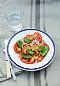 A salad of beef tomato with red onions, spinach and garlic croutons