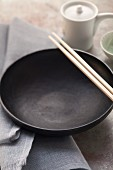 Leere schwarze Essschale mit asiatischen Stäbchen