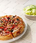 Pizza mit Salami, Paprika, Käse und Oliven, als Beilage Kopfsalat