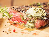 Rump steak with herb butter on a wooden board (close-up)