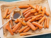 Oven-roasted baby carrots with balsamic vinegar, on the baking tray