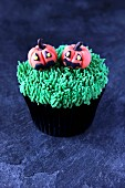A Halloween cupcake with pumpkin decoration made from marzipan