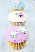 Three pastel-coloured cupcakes with glacé icing and sugar flowers