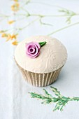 A cupcake with glacé icing and a sugar flower