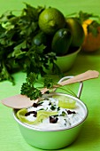 A quark dip with cucumber strips, parsley and black olives