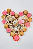 Cupcakes, Biscuits, Backutensilien, Schokolade und Mehl, arrangiert in Herzform