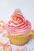 A pink cupcake decorated with rose petals and silver balls