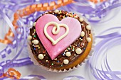A cupcake decorated with chocolate icing and a pink heart between streamers