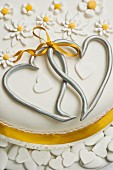 Wedding cake with silver hearts and sugar flowers
