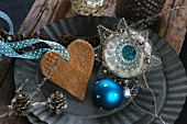 Christmas decorations for the tree: a blue bauble, a salt-dough heart and vintage hanging decorations