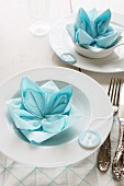 Decorative place settings with lotus flower napkins and hand-crafted, modelling clay pendants with initials as name cards for guests