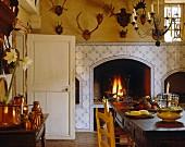 Rustikale Landhausküche mit offenem Kamin, Fliesenwänden & Tiergeweihen