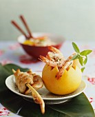 Marinated prawns in a hollowed-out grapefruit, and a satay skewer